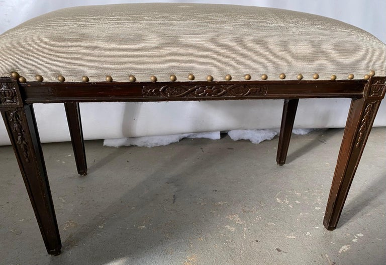 The upholstered bench can be used as a piano bench, vanity bench or extra seating when or wherever needed. Wonderful carved details giving it extra interest. Be it Sheraton, Regency, Hepplewhite or Hollywood Regency, this bench will be a wonderful