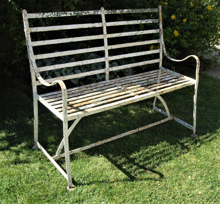 Good Regency wrought iron, slatted garden seat or bench of small proportions; the gently sloping back of slatted form with scroll down arms. The seat with close slats above a hooped stretcher, raised on a traditional 'H' stretcher; the legs