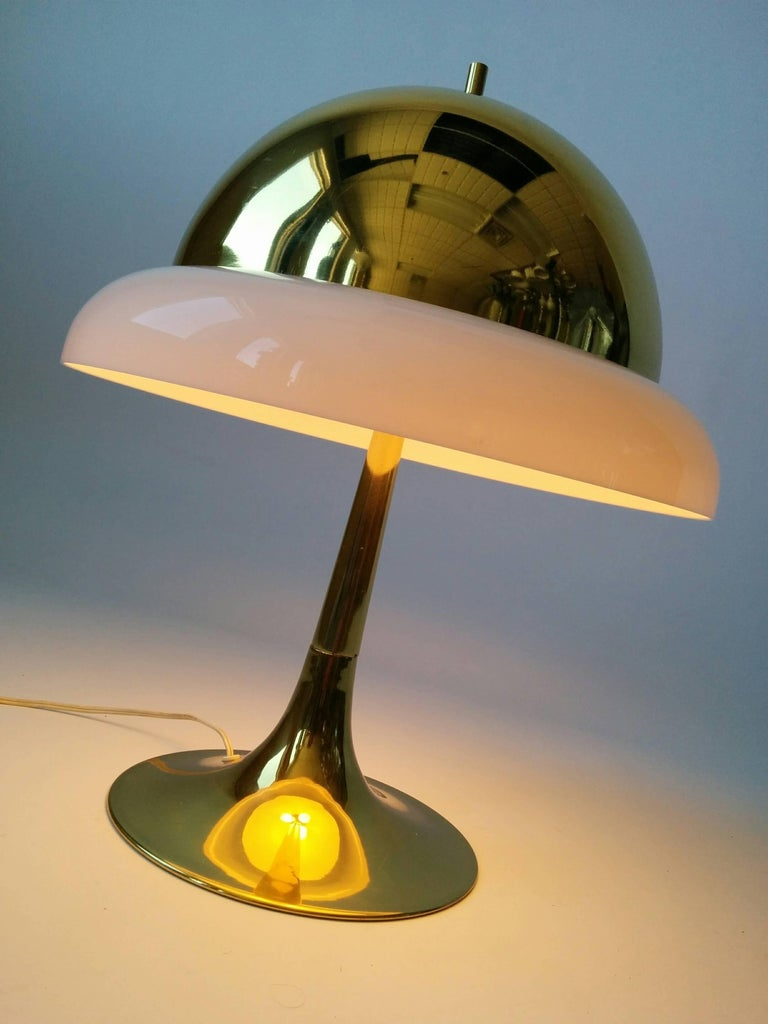 Cozy brass table lamp with a Perspex outer ring sitting on the edge of shade giving it a warm intimate feel.  Three candelabra size socket.