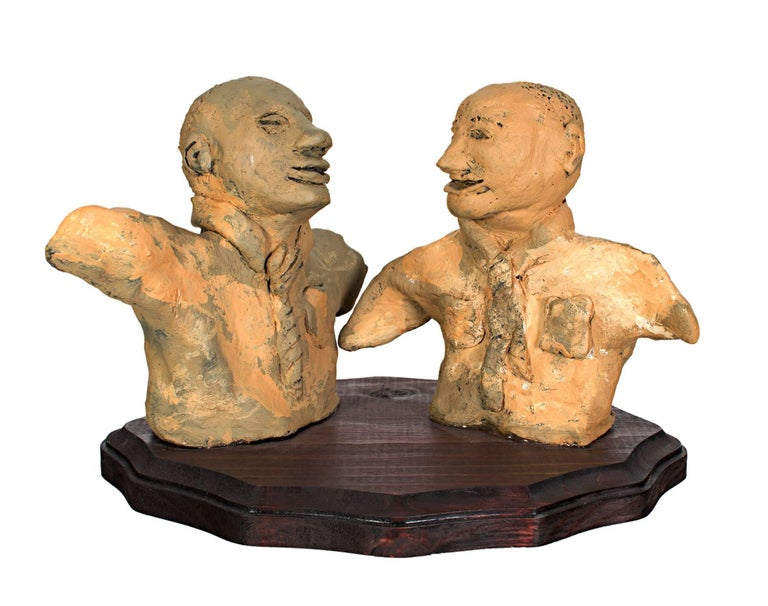 """""""The Merger Will Have Its Ups & Downs"""" is an original clay sculpture painted with acrylic paint by Reginald K. Gee. The sculptures are on a stained wood base. This sculpture depicts two businessman busts. The artist signed it on the bottom.   6"""" x"""