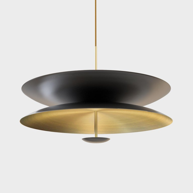 Finely hand-spun brass plates make up this pendant light, finished in a mixed patina. One side is dark end color bronze and the other a gently brushed brass gradient. The light is projected into the shade and reflects out, illuminating without