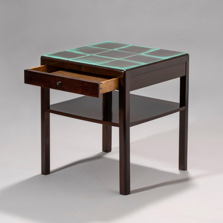 The square top composed of black and turquoise glazed ceramic tiles, set within a ebonized birch frame, the single drawer frieze centering a circular pull, above a shelf stretcher, raised on quarter-rounded legs.   Stamped underneath with the