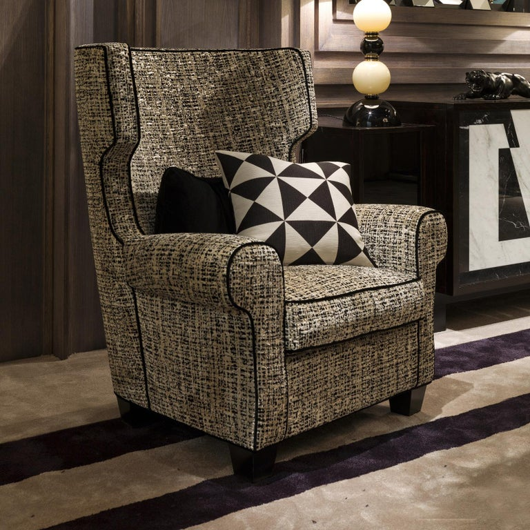 Getting its name from its comfortable silhouette, featuring a tall backrest with a convex, enveloping shape and plush armrests, this armchair is a precious addition to a study or living room. Either to seat with a good book, or to entertain in a