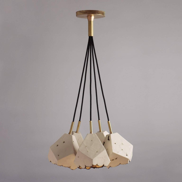 This sculptural chandelier features five geometric porcelain pendants with a unique textural matte finish, and custom brass hardware. The shades are each handcrafted from slabs of unglazed white porcelain with highly individual black oxide burnout