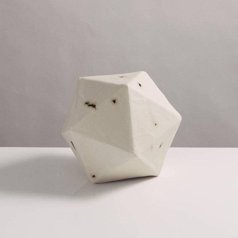This sculptural geometric icosahedron is handcrafted from slabs of unglazed white porcelain with highly individual black oxide burnout detailing, giving each of its 20 sides a unique textural matte finish. The organic texture contrasts with the
