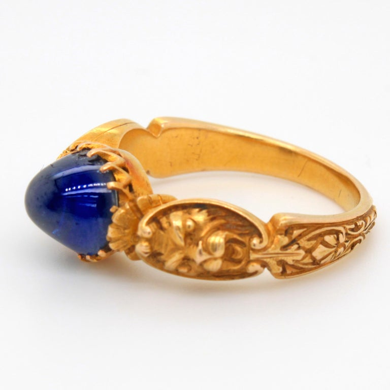 An antique Neo-Renaissance sapphire and gold ring. ca. 1840s. The sapphire cabochon weighs approximately 4.7 carats, is natural (not heat treated) and has a deep royal blue colour. It has some abrasions/feathers and the inclusions show signs of