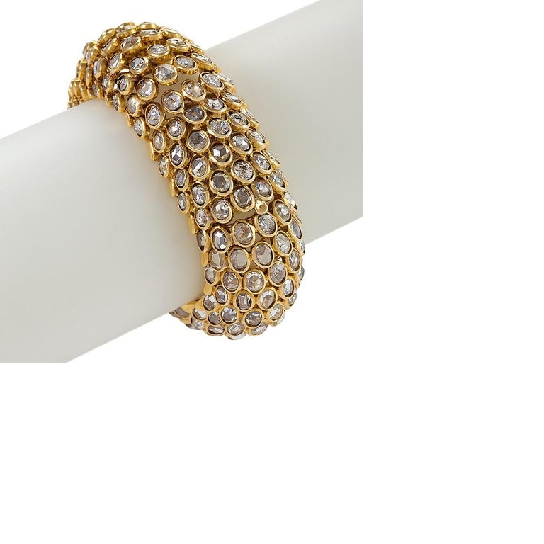 An 18 karat gold bracelet watch by René Boivin. The watch has 252 rose-cut diamonds that have the approximate total weight of  42.25 carats. The bracelet is executed in Boivin's famed fish-scale design, with angled tiers of oval-shaped rose-cut