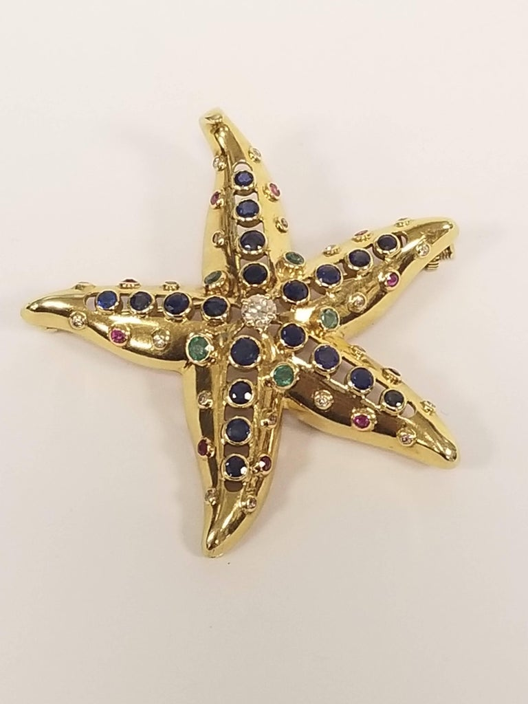 A French 18 karat gold starfish brooch with sapphire, diamond, emerald and ruby by René Boivin. The brooch has 20 sapphires with an approximate total weight of 1.55 carats, 21 diamonds with an approximate total weight of .65 carat, 5 emeralds with