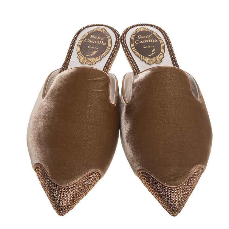 Leave your audience spellbound with this pair of René Caovilla flat mules. These velvet mules have been styled with perfection just so a diva like you can flaunt them. Beige in color, the pair has been designed with pointed toes and open backs,