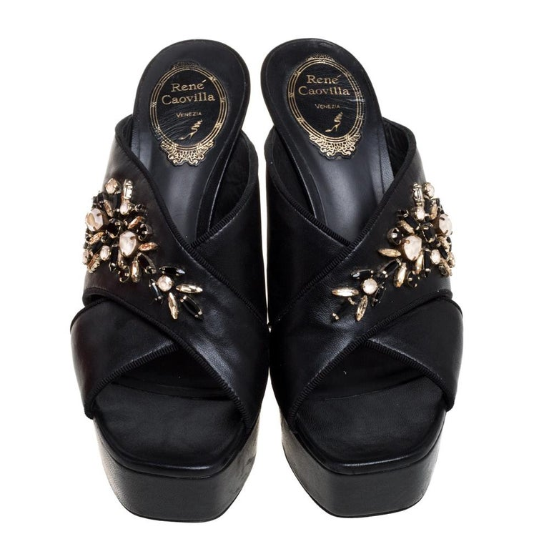 Designed with squared peep toes and beautiful crystal embellishments on the crisscross straps, these René Caovilla mules are simply divine! They've been beautifully crafted from leather in a mesmerizing black hue. They are styled with leather-lined