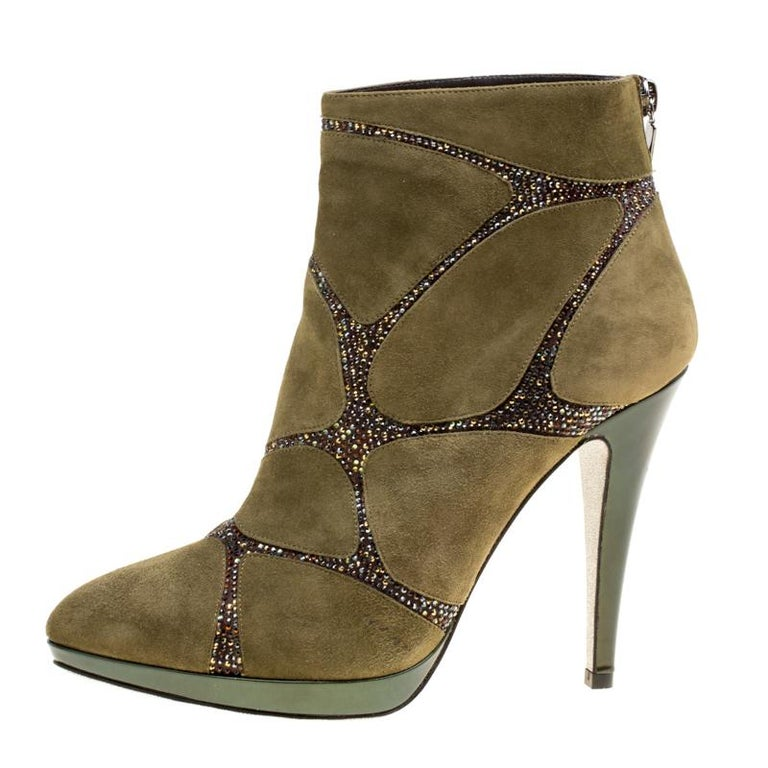 Take your shoe game a notch higher with these ankle boots from René Caovilla. Crafted from suede in a khaki green hue, they are adorned with crystal embellishments on the uppers in an interesting fashion. They feature pointed toes and leather lined