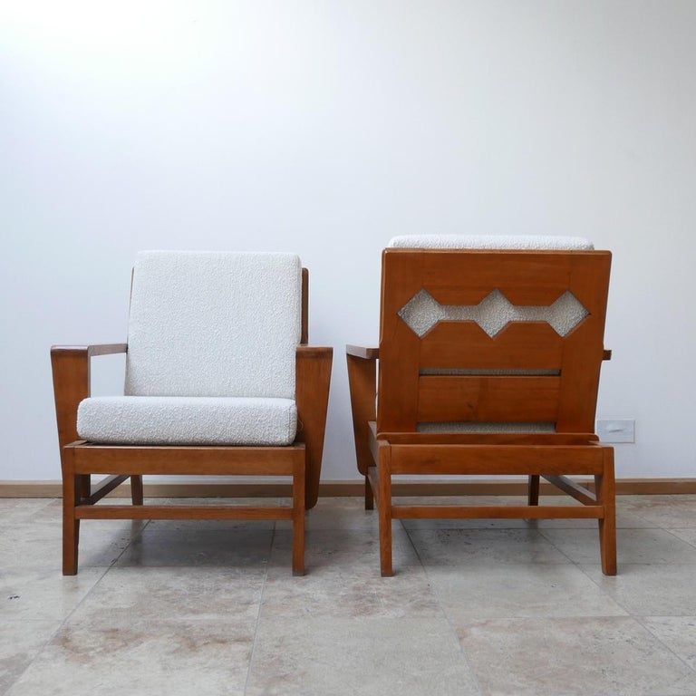 A pair of rare armchairs attributed to René Gabriel.  Re-construction period, circa 1940s, French.  Re-upholstered with an off white boucle fabric.  A scarce model not seen before but with the characteristic kicked out legs.  Dimensions: 74