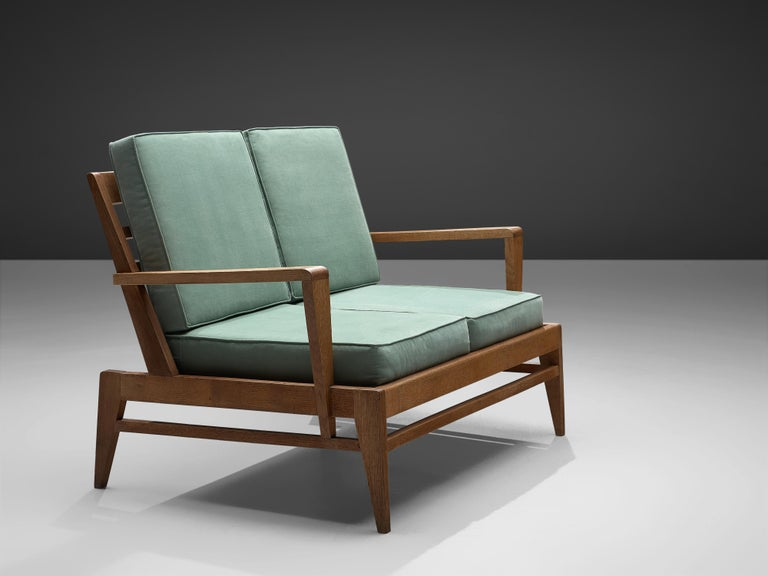 Rene Gabriel, settee, oak, turquoise fabric, France, 1950s.  This French sofa in oak has a solid yet elegant design focused on form and striking appeal. This architectural piece would fit perfectly indoor, as well as outdoor at a patio. The sofa is