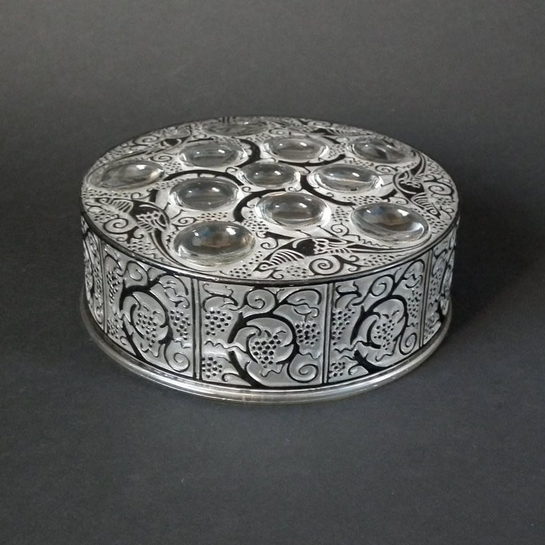 Rene Lalique clear and frosted glass box, with black enameled details. 'Roger' pattern, features stylized fruiting trees and exotic birds. Moulded makers mark, 'Lalique'. Engraved, 'R Lalique France' to underside rim of the lid. Book reference: