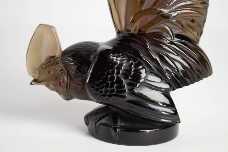 Rene Lalique Mascotte Coq Nain: 19.5 cm tall dark gray also Topaze rooster figure with high tail feathers on incorporated round base R. Lalique Mascotte. Bibliography Model created in 1928 H.: 21 cm Catalogue raisonné F. Marcilhac, ref: 1135: