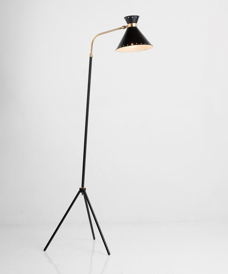 Rene Mathieu floor lamp, France circa 1950.  Black tripod base with brass plated metal neck and perforated black shade. Produced by Lunel.