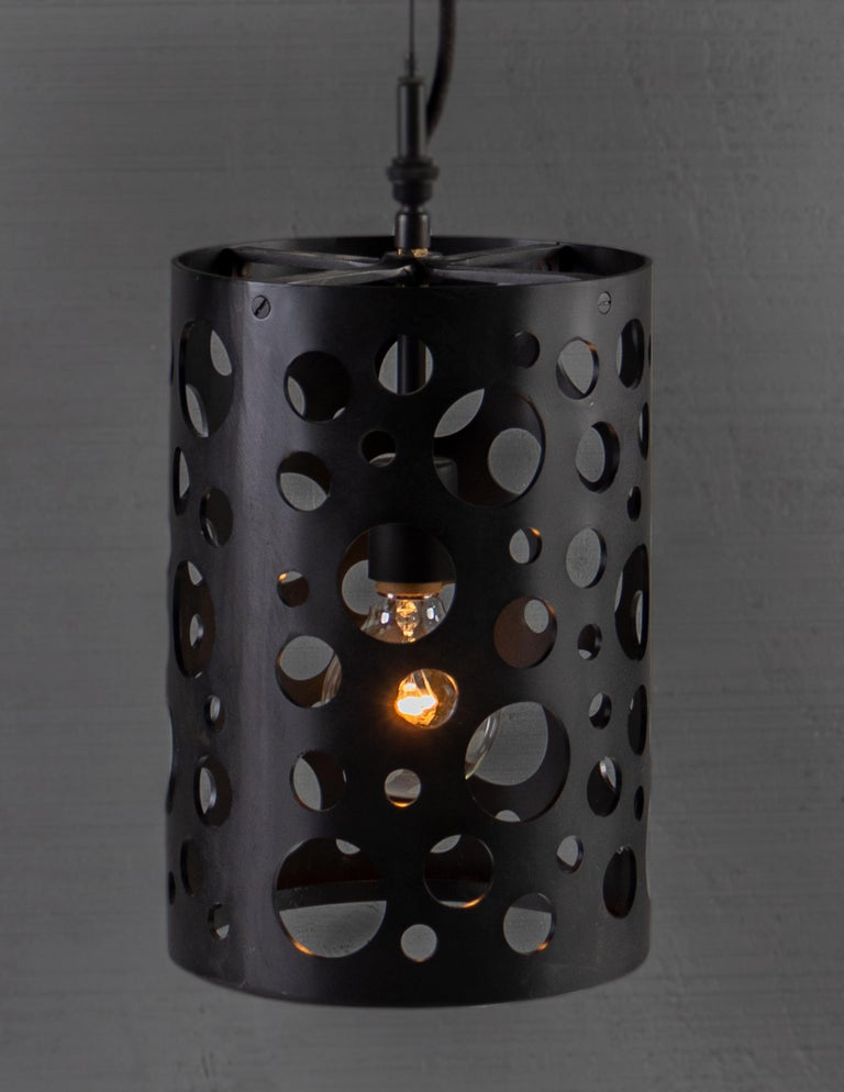Punched steel, random circles. Perforated circular cut outs on cylindrical body pendant light.   Bulb 1x medium base 75 watt incandescent.   Handcrafted in Italy. Sold exclusively at Brendan Bass.  Minimum hanging height: N/A Maximum hanging height