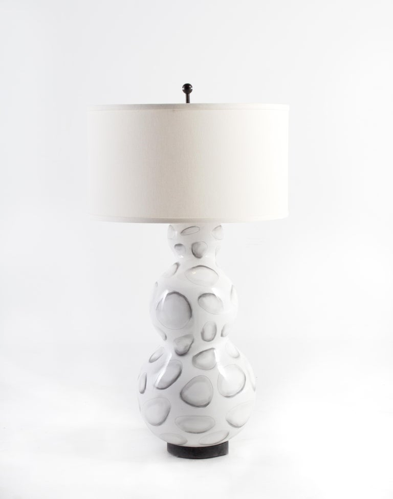 Lamp, gloss white glazed ceramic with stylized shell design   Off-white linen shade. 32