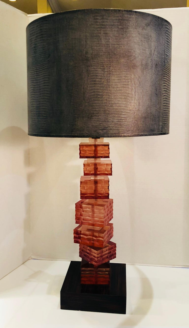 Striking acrylic lamp was pictured in architectural digest magazine and is a work of art!  Chic modernist table lamp features a stack of 7 honeycomb textured Lucite blocks of varying sizes in a cognac amber color, alternating with 7 smaller Lucite