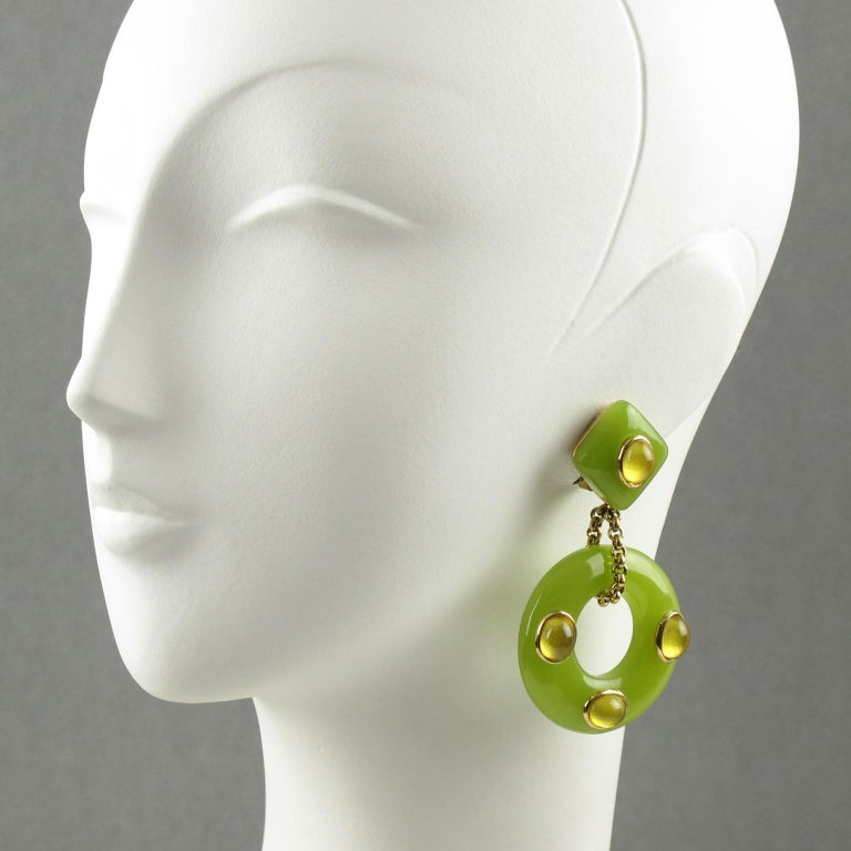These lovely resin dangling clip-on earrings by Replica Italy are certain to enhance the beauty and elegance of any collection or outfit. They are made of gold plated metal set on dangling resin donut in apple green color topped with vaseline resin