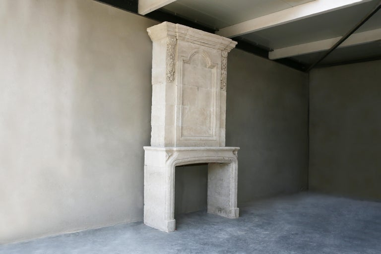 Nice replica fireplace made of French limestone including trumeau. The fireplace is made of French limestone and is made in the style of Louis XIII. There has been a small break in the front section, but it has been restored so well that you can no