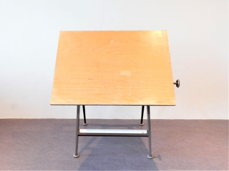 This 'Reply' drafting table was designed by Friso Kramer and Wim Rietveld for Ahrend de Cirkel in the 1950s. It has a brown lacquered steel frame and a ply wooden top that is adjustable from vertical to horizontal position by 2 rotary knobs. We have