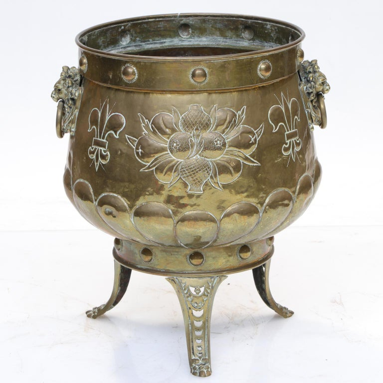 A Repousse brass planter on a three-leg stand. Very nice quality detail with fleur-de-lys, coat of arms, and vase with leaf. There are two very nice lion mask handles with rings. Notice the three pierced support legs. It seems to be sealed tight and