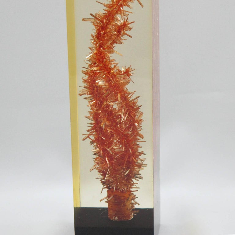 Resin table lamp by French artist Pierre Giraudon. Orange faux coral inclusion, embedded within layered poured resin with black resin base. Natural yellowish coloration of the material due to time. No visible marking. Lamp has been rewired to fit US