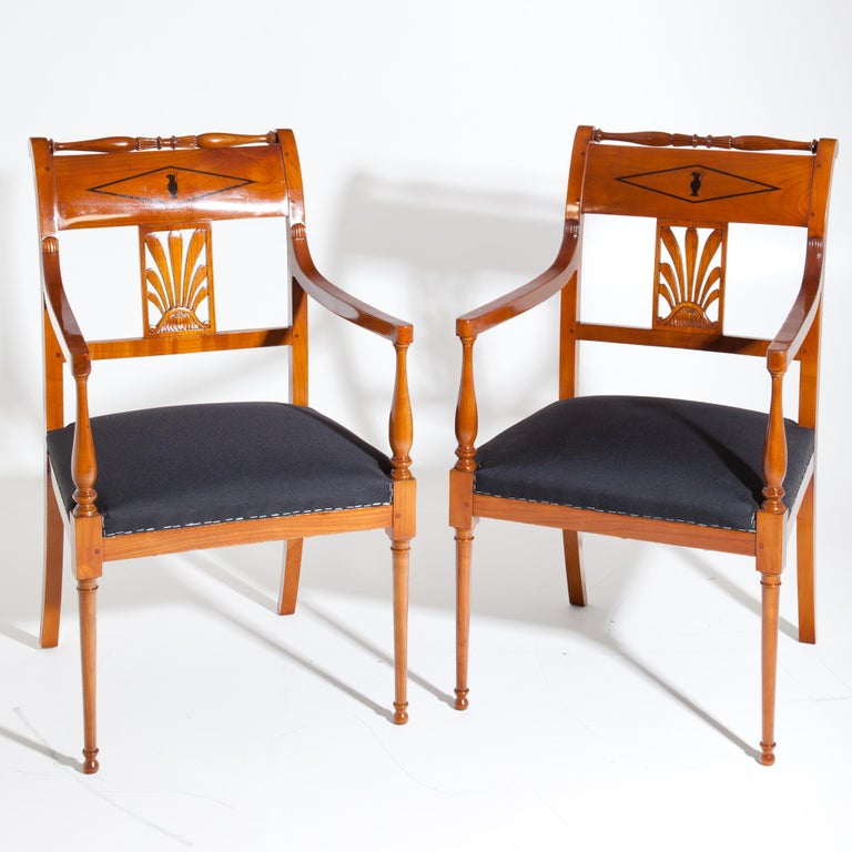 Pair of restoration armchairs made of solid cherry wood standing on conical legs in the front and slightly flared sabre legs in the back. The armrests rest on baluster-shaped supports, the backrests show further baluster-shaped elements as well as