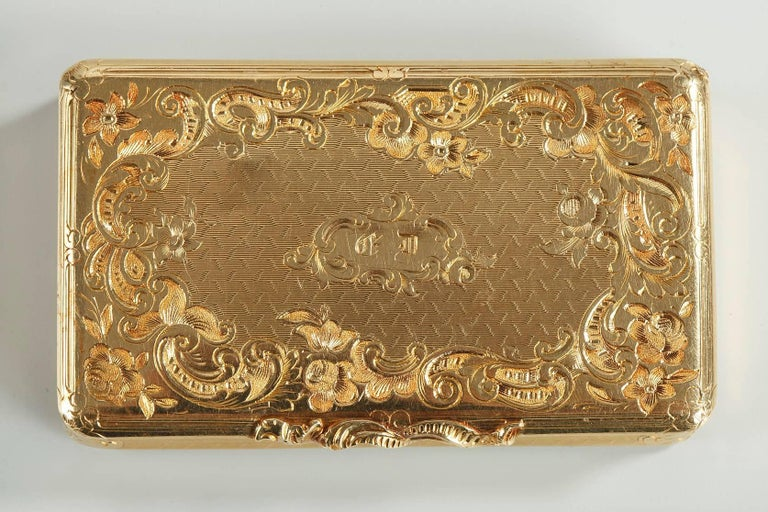 Small, gold snuff box featuring Rocaille motifs. Its cover is embellished with delicately sculpted scrollwork and asymmetrical flowers, which revisits the Rocaille repertoire that was in vogue during the reign of France's Louis XV. An intricate