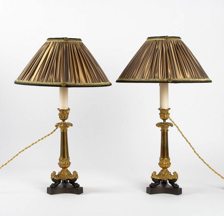 French Restoration period, converted in table lamps, pair of small bronze candlesticks.  An elegant et decorative pair of small chiseled gilt and patinated bronze candlesticks. Original gilt. Lovely antique chiseled decoration with Acanthus leaves