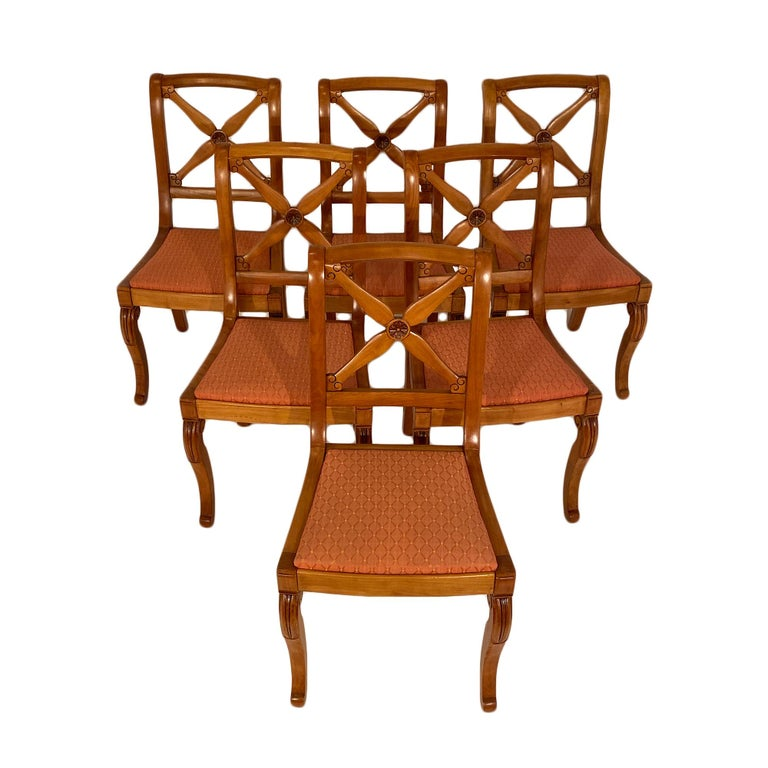 French Restoration dining chairs with additional two armchairs. All are made of hand carved cherrywood with very strong frames. They feature saber back legs and console front legs. The opened back is adorned with stylized crossing swords.