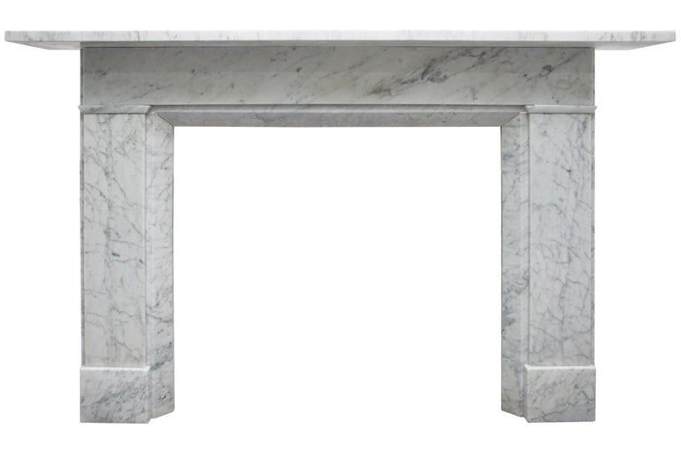 A restored antique mid Victorian Carrara marble fireplace surround of simple construction with chamfered inside returns, circa 1850.   Pictured with an original cast iron insert, sold separately.