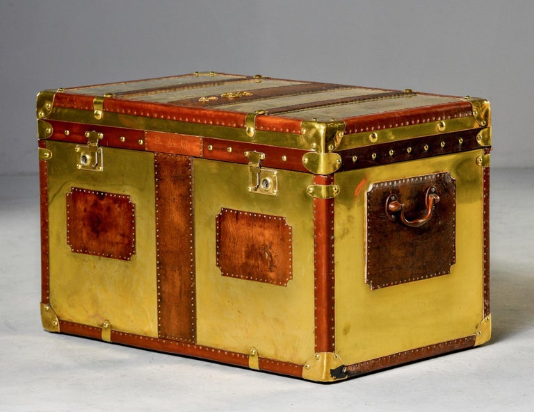 English brass and leather trunk with hinged lid circa 1930s. Wooden trunk is covered in weathered leather and polished brass and English grenadier's ornamental details. New royal blue fabric lining and restored leather interior. Unknown maker.