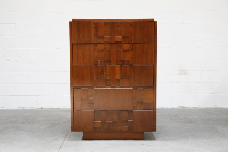 This fully restored Mid-Century Modern Brutalist highboy dresser, created by Lane, features a cubist style wood arrangement across the front of the five dresser drawers. Each of the blocks of wood has a rich and unique grain, each going a different