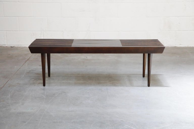This lovely Mid-Century Modern expandable slatted wood bench (which can also double as a coffee table or low console) has been fully refinished and features rows of expandable slatted wood and four tapered legs. This George Nelson for Herman Miller