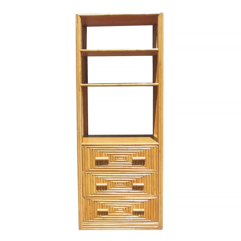 Three-tier stick rattan display cabinet with mahogany shelving and side panels, circa 1940. This large 7' tall cabinet features three fixed shelves and a bottom cabinet which has three drawers for storage. Perfect for use as a focal point in a