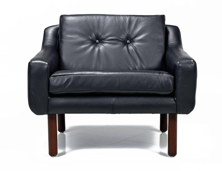 Fully restored with new luxurious black leather. This Mid-Century Modern lounge chair had no marking, but it's clearly in the style of Frits Henningsen and Svend Skipper, made in the 1960s. This low-back armchair features a sleek profile in the