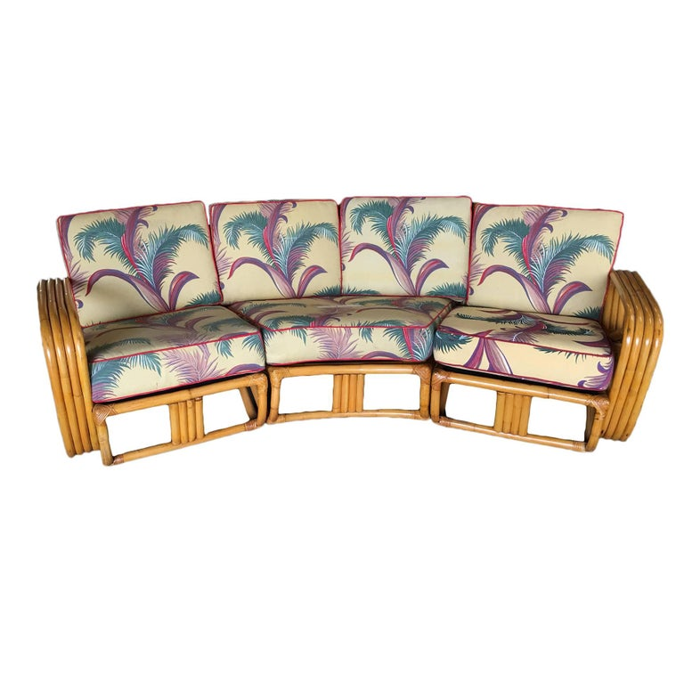 Four strand square pretzel corner rattan sectional sofa designed in the manner of Paul Frankl. This sofa features a bent rattan base with four strand square pretzel arms and is divided into a three sectionals, two end pieces that each fit one person