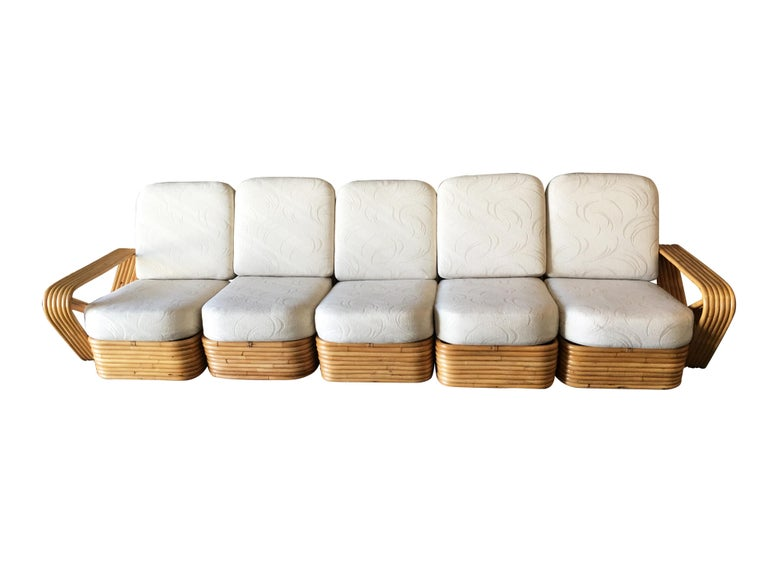 Paul Frankl style five-strand square pretzel style, five-seat sectional sofa. This sofa features the famous six-strand square pretzel side arms and stacked rattan base originally designed by Paul Frankl. The seats are covered in palm leaf pattern