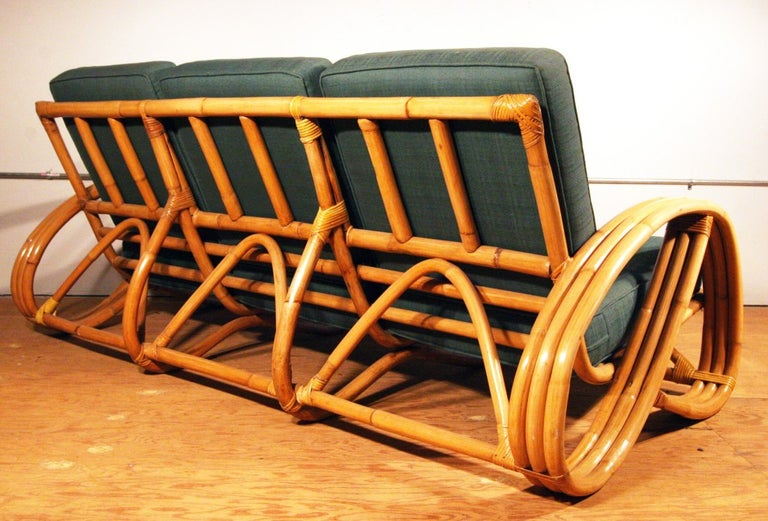 Paul Frankl styled post-war three-strands, 3/4 pretzel arm rattan sofa features a decorative wave detail around the perimeter of the base. Restored to new for you. All rattan, bamboo and wicker furniture has been painstakingly refurbished to the
