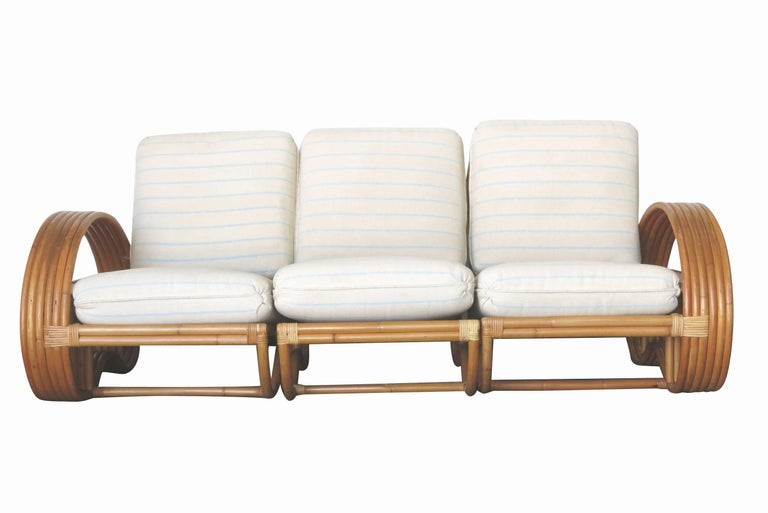 As seen on the cover of architectural digestSeptember 2019   A full rattan living room set featuring a three-seat sofa with two matching lounge chairs, each with unique six-strand arms inset with a mahogany shelf.   Three-seat rattan sofa: 31in.
