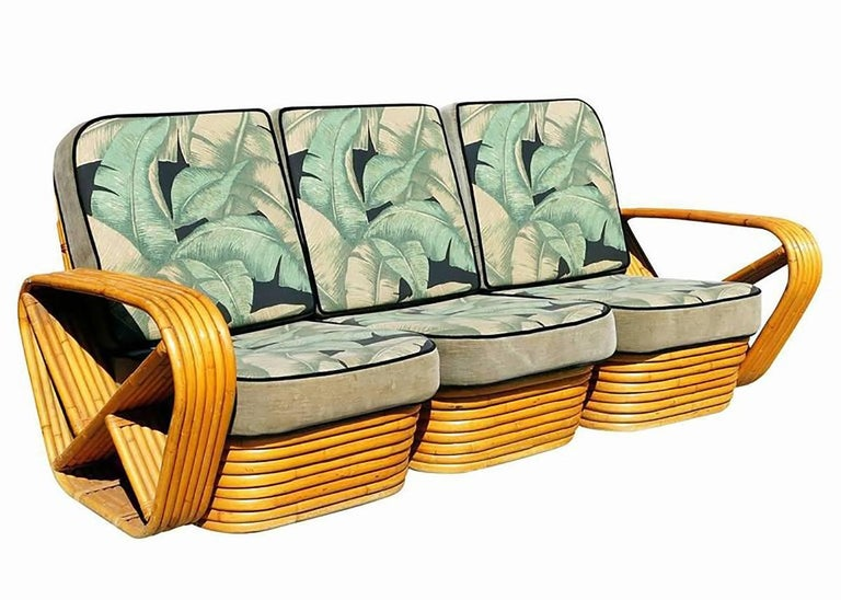 Paul Frankl style rattan living room set including a matching three-seat sectional sofa and a pair of lounge chair. Both feature the famous six strand square pretzel side arms and stacked rattan base originally designed by Paul Frankl. The seats are