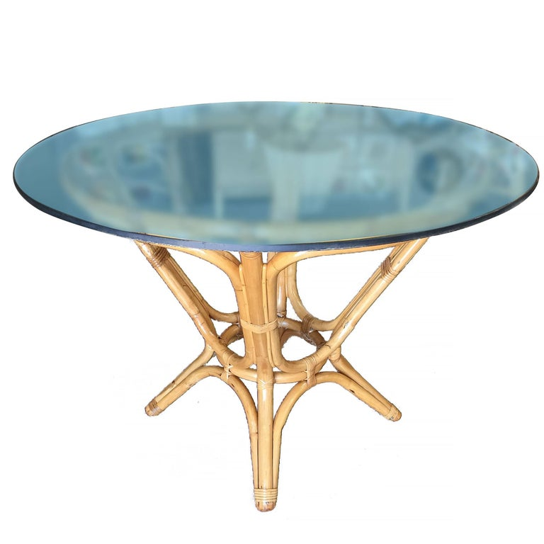 Elegant midcentury dining table features a sculptural hourglass rattan base with a round glass top. The table can easily accommodate four guests depending on the choice of chairs.