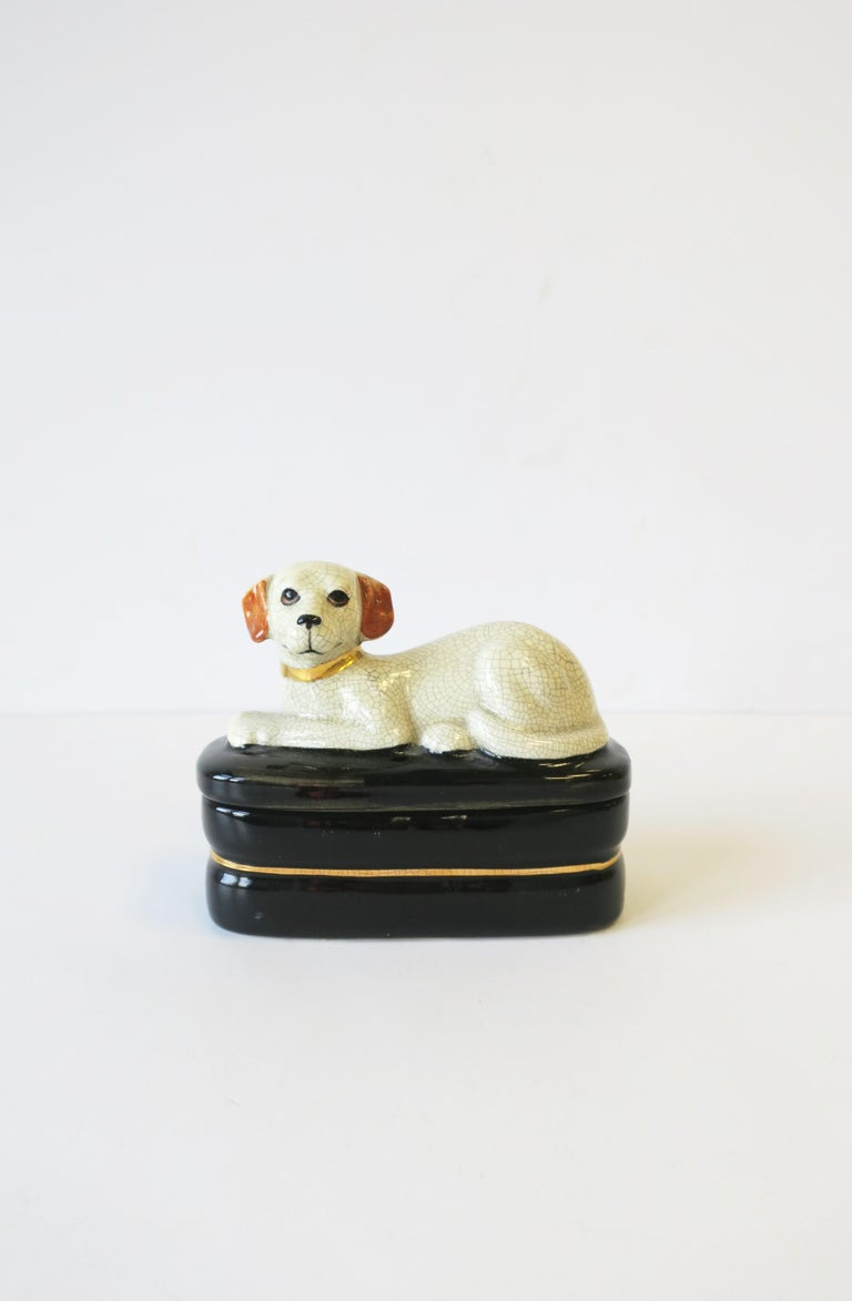 A ceramic retriever dog on pillow decorative box. Great as a standalone piece or to hold small trinket items or jewelry. Colors include: Off-white, black, gold, and touches of brown on ears. A great piece for a console, desk, vanity, nightstand