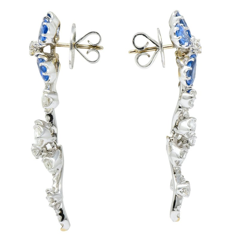 Earrings designed as two articulated flowers, one with sapphire petals and the other with diamond petals  Top flowers contain petals comprised of pear cut sapphires weighing approximately 4.80 carats total, transparent and cornflower blue  Lower