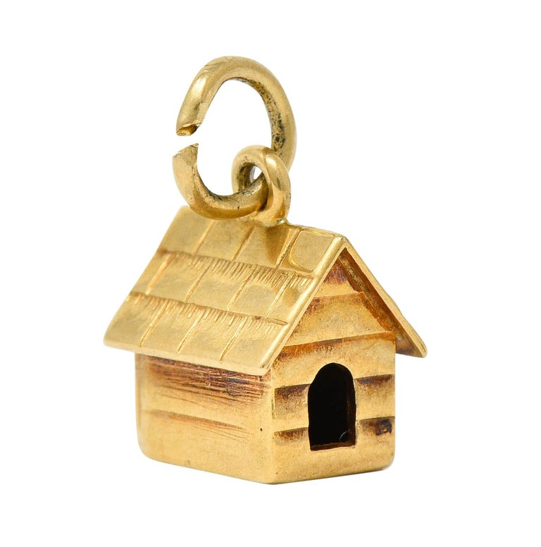Charm is designed as a pitched roof doghouse  With deeply engraved shingles and siding  Completed by a jump ring bale  With maker's mark and stamped 14K for 14 karat gold  Circa: 1950s  Measures: 1/4 x 5/16 inches  Total weight: 1.3 grams  Cute.