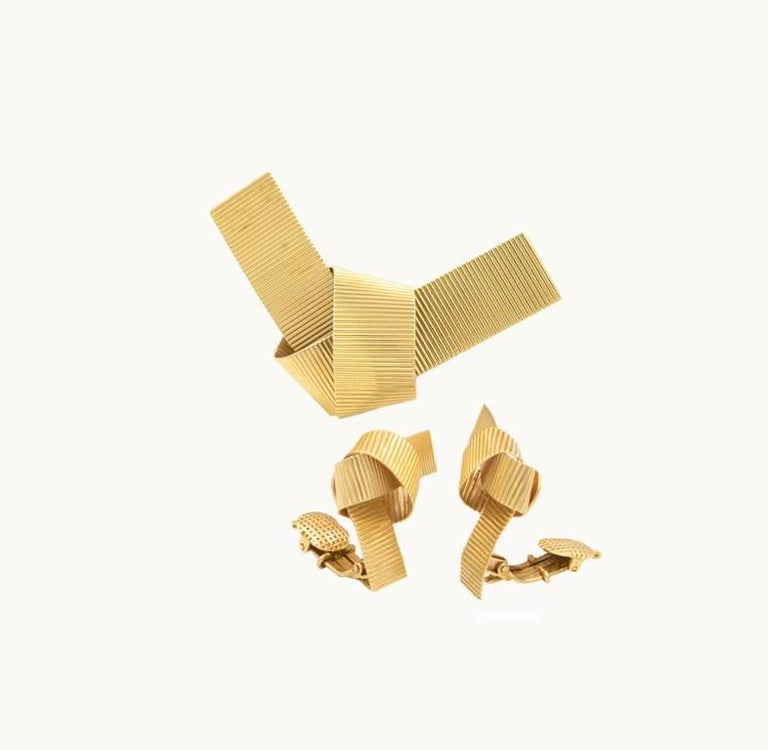 A vintage retro bow style set in 14 karat yellow gold with ribbed gold design from circa 1950.  This set includes a matching bow brooch and clip-on earring set.  Brooch measures approximately 2.36 inches in length and 1.45 inches in width.  The
