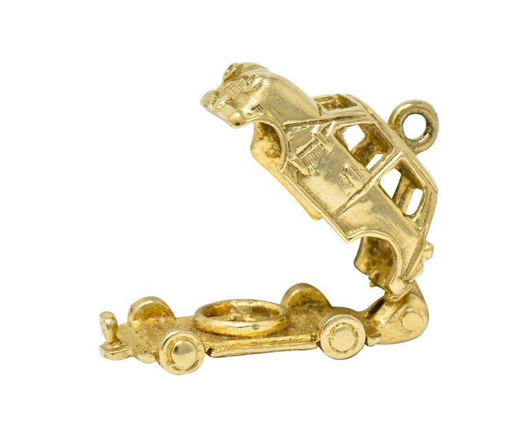 Designed as a retro style car with pierced windows and highly rendered details  Base of car opens on a hinge to reveal a spare tire  Tested as 14 karat gold  Circa: 1940s  Measures: 3/8 x 7/8 inch  Total weight: 4.4 grams  Enjoyable. Family.