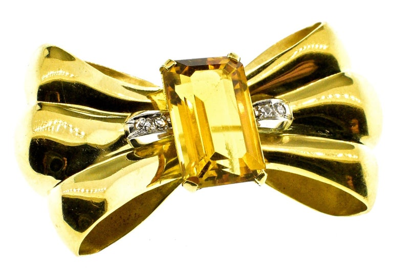Retro 18K gold brooch centering an emerald cut natural bright citrine weighing approximately 10 cts. and accented on both sides with small white diamonds.  This three dimensional piece is 1.75 inches long and weighing 16.27 grams.  Circa 1950 in